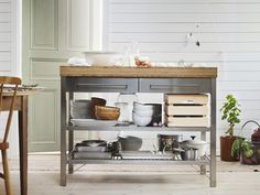 A work bench with bamboo worktop and stainless steel underframe with shelves and drawers.