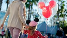 A mother holds hands with her daughter who wears a Minnie Hat and has a Mickey balloon