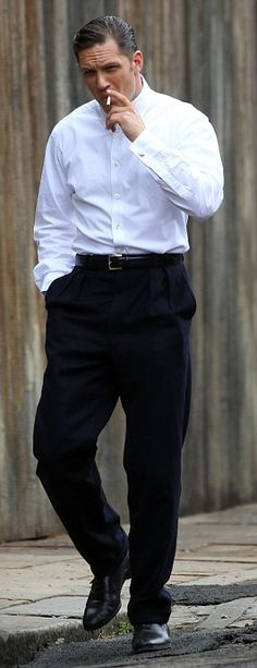 Smoking hot: The actor wore a white shirt and classic suit trousers as he puffed on a fake cigarette during filming