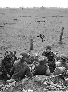 Sergeant F. Beal (fourth from left), Canadian Army Film and Photo Unit, talking with infantrymen of the Royal Hamilton Light Infantry (R.H.L.I.). March 24, 1945, Speldrop, Germany.
