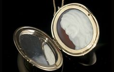 Gold locket in the clamshell design which can be opened to reveal the cameo portrait contained inside.