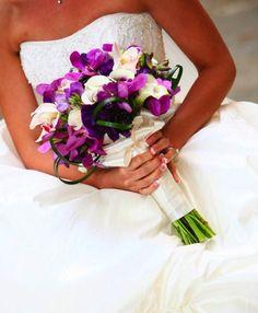 This bouquet includes mokara, cymbidim orchids, lisianthus, scabiosa, freesia, calla lilies and lily grass.