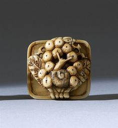 """IVORY NETSUKE 19th Century In the form of fruit and a snail resting on a wicker basket. Length 1.4"""" (3.6 cm)."""