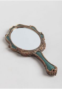 Natural Beauty Hand Mirror   Modern Vintage New Arrivals   Beautifully designed and antique-inspired, this teal and gold-toned hand mirror features an ornate design with leaves and rivet details