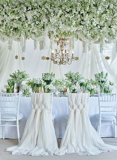 Luxe white wedding reception with floral canopy, tulle draped chair backs, lily of the valley, hanging place cards and chandelier. Styling, Laura Burkitt. Florist, Wildabout Flowers. Photography, Catherine Gratwicke for Brides magazine