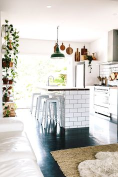 White kitchen with beautiful tiling on island and hanging cutting boards