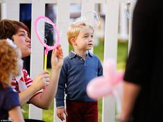 Prince George looks in awe as giant bubbles are blown into the air by one of the children'...