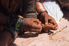 Himba woman making jewelry Stock Photo