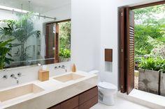 Amplitud y claridad dominan el baño principal, donde las líneas de corte moderno conviven con la vegetación interior y la vista del entorno.