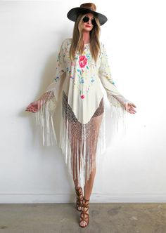 Inspired by 70's rock goddesses! Incredibly flattering bias shape drapes the body beautifully with extra long dramatic fishnet fringe creating heavenly movement! Stunning hand embroidered silk crepe de chine Spanish shawl was used to make this beauty in an antique ivory with a gorgeous bright floral motif. A truly magical piece that can be dressed up or down and transcends any trend making this a piece to treasure for a lifetime ❤100% SilkOne size fits mostDry clean only
