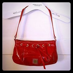 SALE Dooney & Bourke red purse Patent leather red Dooney & Bourke purse in great condition! Fits perfectly over your shoulder and has a spacious inside. 10 inches in length and 6 inches vertically. Has a tiny knick in the front but not noticeable.  The inside cloth has a few marks but nothing noticeable either! Dooney & Bourke Bags Shoulder Bags