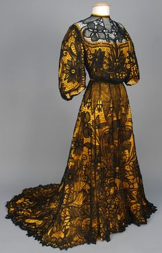 Circa 1902 Battenburg Lace Afternoon Gown: Two-Piece Black Lace Over Marigold Cotton Sateen Having Pigeon Breasted Bodice With 3/4 Bell Sleeves and a Trained Skirt With Deep Hem Flounce. Via Whitaker Auctions.