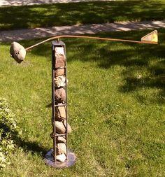 Kinetic yard art, rebar, stone, and recycled metal.