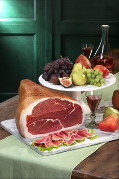 A whole leg of Prosciutto presented next to sliced Parma ham and a platter of Italian fruit. Looks like a shot from the 70's