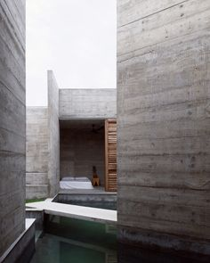 From outside, the building appears as an entirely solid concrete mass, punctuated on one side by a pair of openings containing sturdy wooden doors.