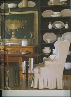 Country French dining room with black built-in shelves that hold a collection of white ironstone dishes
