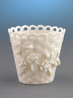 This delicate Belleek pierced spill vase takes the form of a woven basket. Crafted of Irish clay and fired using traditional methods, this charming vase displays a pieced, loop rim and features the carefully applied floral decoration for which Belleek is famous. Belleek baskets were first created from designs by renowned basket weaver Michael Maguire, who first brought his skill and ingenuity as a figure maker to the Belleek firm in the 1880s. Uniting the intricate arts of basketry and…