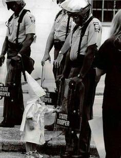 """""""Irkçı KKK yürüyüşünde bir çocuk siyahi polisin kalkanıyla oynuyor,ABD,1980ler..."""""""