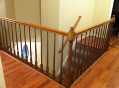 Cheap way to child proof a stairway with banisters which are too wide. Use $20 plastic chicken wire (contractor fencing) found at Home Depot and zip ties.