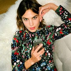 Alexa Chung wearing black dress with multicolored floral embellishments.