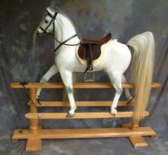 A very upright, trotting horse on a natural oak stand with Arabian tail and natural dappling.