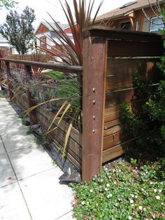 Modern low fence with wood at bottom, horizontal wires and nice metal details. What I love about this fence is how you can see through to the house; it visually allows for more flow and a feel of openness. Plants in front of the wire could or could not happen, depending.