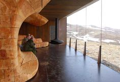 The mythical landscape is reflected in part by a tremendous wooden wall inserted into the core of the pavilion.
