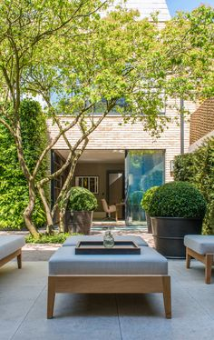 Serene courtyard beyond home extension with glazed sliding doors. Over-sized planters and chunky outdoor furniture give solidity. Design by Luciano Giubbilei. Planters by John Desmond Ltd in PVD stainless steel.