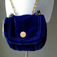 """Juicy Couture Cobalt Velvet Crossbody Super soft little bag. The cobalt blue has a purple tone to it  / color is best rep'd in the cover photo. Approx measurements: depth 2.5"""", length 7.5"""", height 7"""", strap drop 24"""". Very heavy bright gold chain, with cobalt leather strap at the top/center of strap. Bright gold hdwe. Faceted jewel clusters w a gold metal Juicy Couture crown flat bead. Closure under the flap. Small pkt under flap, zip pkt inside, pocket on back. NWT. Gorgeous and clean inside…"""