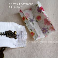 Step 4 Trim the zipper ends to 1/2″ seam allowance from the stops. Fold the 1 1/2″ square fabric into half then fold a seam allowance of 1/4″.