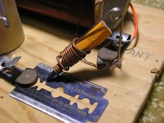 """Crystal Radios / Fox Hole Radios: For me, it all started here   N6CCAbove: Showing the detail of the safety pin used to hold the pencil lead against the razor blade. The copper wire connects the """"lead"""" to the safety pin and the antenna circuit. This assembly functions as the """"Cat's Whisker"""" of classical crystal radios. My cat was especially appreciative of this alternate design."""