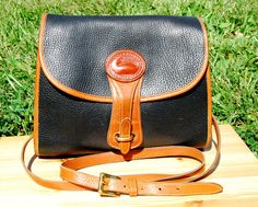 """This fantastic black and tan pebbled leather crossbody bag/satchel is an original Dooney & Bourke Essex bag. It was made in the U.S.A. around the early 1990s.   •  Black Pebbled Leather exterior with Tan trim and Unlined Leather interior •  2 interior small zippered pockets, 1 small slip pocket; 1 back slip pocket w/ brass fastener •  Solid brass hardware, buckles & duck hang tag •  42"""" inch adjustable strap with brass fasteners (24"""" strap drop, 3 notches) •  10"""" length x 9.5"""" height x 3.5""""…"""