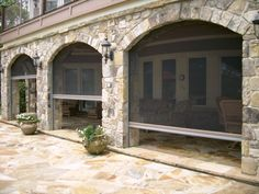 stone arched patio with retractable screens