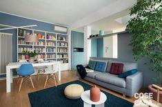 zona giorno open space del sottotetto su due livelli, tavolo da pranzo bianco, sedie design anni '50. libreria, radiatore d'arredo, divano grigio, tavolino bianco, parete divisoria di colore grigio-azzurro