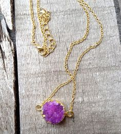A dainty purple crystal quartz druzy hangs horizontally from a gold colored chain. The druzy's edges has been electro plated with gold. This is a dainty necklace, elegant, and edgy. The chain is about