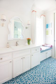 Contemporary kid's bathroom boasts a built-in window seat topped with blue cushion and pink and purple ikat bolster pillows under window dressed in short curtains with red ribbon trim atop tone on tone blue geometric tiles.