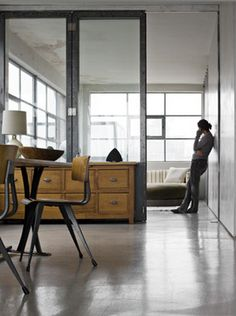 love the texture of old chest of drawers against glass walls.  love the chair too