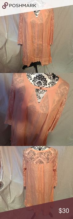 Women's blouse Brand new women's blouse size medium, oversized. Peach in color with keyhole cutout in front with button. Lace sleeves and top of back is lace. Also has a slightly ruffled trim around bottom. Has pockets on each side. Tops Blouses