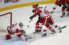CHICAGO IL - MAY 29: Marian Hossa is hit by Kyle Quincey and Henrik Zetterberg in front of Jimmy Howard