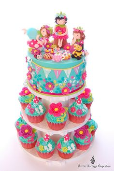 Love, love, love this cake and cupcake tower with a fairy picnic!!!!! Such bright colors!! Cute idea :)