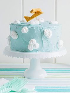 "Top a cake with light blue frosting, meringue ""clouds,"" and a plane made from vanilla sugar wafers for a heavenly birthday cake."
