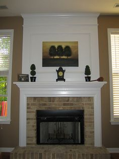 More formal version of a fireplace with windows in either side.