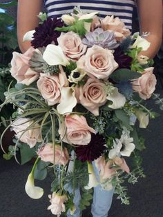 This amazing waterfall bouquet was designed with Sweet Eskimo roses, thistle, white calla lilies and anemones, burgundy dahlias and succulents. We were excited to get to incorporate an air fern in there as well!  Candlelight Floral & Gifts, Wayzata MN.