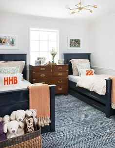 Framed photographs hang from a white wall above glossy navy blue lacquered beds accented with a trundle and dressed in natural linen bedding paired with matching shams and white and orange monogrammed pillows complementing orange chevron throw blankets.