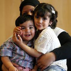 20150505 - A menina síria Tala (dir) abraça o irmão, ambos sentados no colo da mãe, após reencontrá-los no aeroporto de Salônica, na Grécia. Tala, 4, havia sido encontrada em janeiro, abrigando-se do frio ao lado do pai morto, na fronteira entre a Turquia e a Grécia  PICTURE: Sakis Mitrolidis/AFP