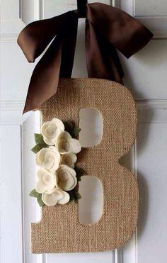 Letras forradas en fique,flores en paño lency y cuelga de un hermoso moño en cinta de seda