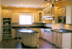 Vanilla painted kitchen with island, wood stove hood, wood post details, glass front cabinets