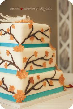 beautiful fall cake. orange and light blue with two doves as the topper.