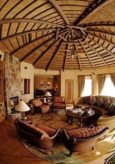 The Royal Asante Suite, is a lavish, oasis with hand-crafted armoires, a cozy curved couch nestled by a remote-control fireplace & a bubbly Jacuzzi, Round House Plans, Curved Couch, African Interior Design, Disney Animal Kingdom Lodge, Cabana, Thatched House, Thatched Roof, Yurt Living, Minecraft Bedroom