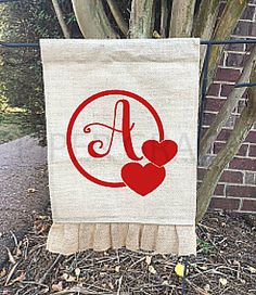 Burlap Garden Flag with ruffle at bottom and 2-heart monogram frame and initial in red heat transfer vinyl.  Garden flag is made of 10 oz. burlap and is approximately 12.5 X 19 with 1.5 Casting for Garden Flag Holder and 2.5 Ruffle (ruffle measurements is included in finished length of 19). Flag is safety stitched on all edges. Back of Flag has a clear coating. THIS LISTING IS FOR THE GARDEN FLAG ONLY. IT DOES NOT INCLUDE THE HOLDER.  To order, choose whether or not you would like a mock up…